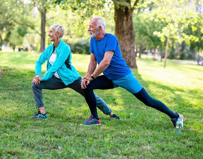 elderly couple stretching outside